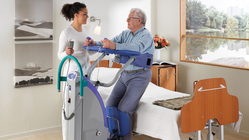 arjohuntleigh-patient-transfer-solutions-standing-and-raising-aids-sara-plus-nurse-helping-patient-off-bed.jpg
